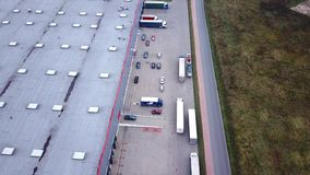 Trucks are Driving to Logistics Center. Aerial Shot./ Storage Building/ Loading Area where Many Trucks Are Loading/ Unloading Merc