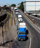 Trucks driving to Port. Column of trucks driving on bridge to sea port Stock Photos