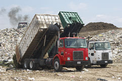 Trucks Dumping Waste. Two trucks unloading garbage at dumping ground stock image