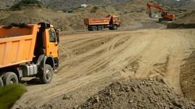 Trucks and excavator working. In public works stock footage