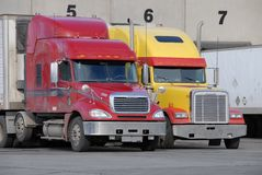 Trucks at fruit warehouse. Red and yellow trucks at fruit warehouse Royalty Free Stock Photo