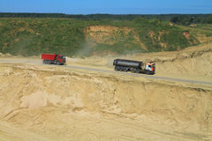 Trucks go down in a pit behind sand. POLEWOJE, KALININGRAD REGION, RUSSIA — JUNE 18, 2014: Trucks go down in a pit behind sand Stock Photography