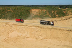 Trucks go down in a pit behind sand. POLEWOJE, KALININGRAD REGION, RUSSIA — JUNE 18, 2014: Trucks go down in a pit behind sand Stock Photo