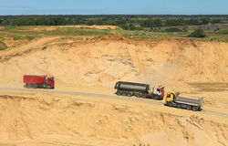 Trucks go down in a pit behind sand. POLEWOJE, KALININGRAD REGION, RUSSIA — JUNE 18, 2014: The movement of trucks in career Royalty Free Stock Image