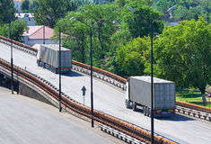 Trucks going up the bridge, cargo transportation, delivery and shipping concept, green trees on background Stock Photo