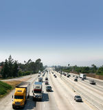 Trucks on Highway. Flowing traffic with trucks forefront.  Both directions of traffic visible across several lanes Stock Images