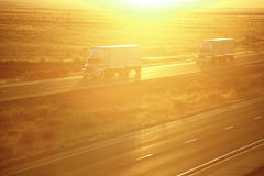 Trucks on highway. Semi trucks on I-40 interstate at sunset Stock Photo