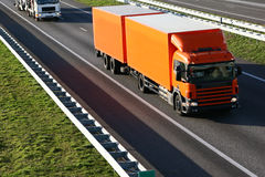 Trucks on the Highway. A large truck on the highway with another one partially visible behind it. Slight motion blur due to high speed movement of the truck Royalty Free Stock Images
