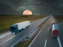 Trucks on highway at night of the full moon Royalty Free Stock Image