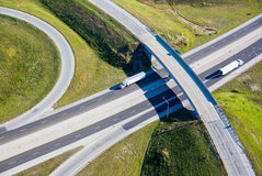Trucks on highway transportation aerial photo. Aerial photo Semi-Trailer trucks passing through clover leaf in interstate highway system royalty free stock image