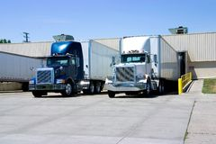Trucks Loading. This is a picture of 18 wheeler semi trucks loading at a warehouse building Royalty Free Stock Photos
