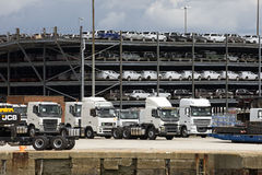 Trucks and luxury cars await export from docks UK Stock Photography