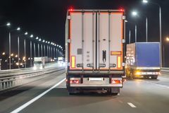 Trucks move on a night freeway. Trucks move on a night illuminated freeway royalty free stock images