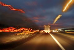 Trucks moving down a highway at night. Leave light trails Stock Photo
