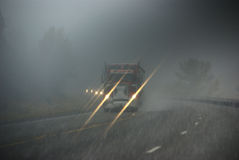 Trucks moving through fog Stock Images