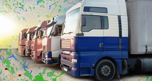 Trucks moving on the highway on a geographical map. Big trucks moving on the highway on a geographical map. Delivery of goods anywhere in the world royalty free stock photos