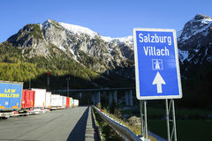 Trucks parked at rest stop. FLACHAU, AUSTRIA - MAY 10, 2017 : A road sign for Salzburg-Villach with parked trucks lined up at the Landzeit Tauernalm highway rest Royalty Free Stock Images