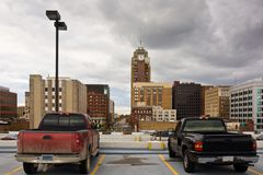 Trucks on parking lot. Two trucks staying on the top of a parking lot. A view of Lansing downtown, Michigan, USA Stock Images