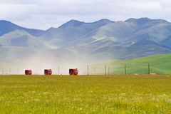 Trucks passing through grassland Stock Photo