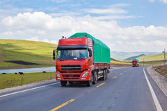 Trucks passing through grassland Stock Photography