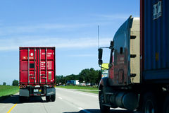 Trucks passing on the open road. Red truck passing a blue truck on an American highway: the arteries and engines of the economy royalty free stock image