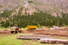 Trucks on the road during repairs after flood in a valley between mountains of Central Asia Royalty Free Stock Images