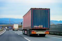 Trucks in road Trucker in highway Lorry doing logistics work. Trucks in road. Trucker in highway. Lorry doing logistics work. Semi trailer with driver. Big cargo stock image