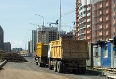 Yellow trucks stand on the roads near the construction site stock photos