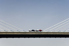Trucks on suspension bridge. A picture of two trucks driving on a suspension bridge. Cars have been loaded on the back of the trucks Stock Images