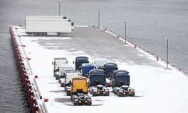 Trucks and trailers waits on snowbound pier Stock Photos