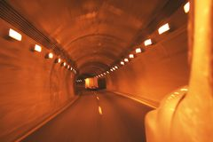 Trucks traveling down the highway enroute to customers. Passing through the curved tunnel at high speed Stock Photo