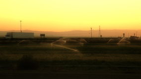 Trucks Traveling Through Fields. A busy road through an agriculture area stock footage
