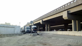 Trucks under bridge from a distance. At afternoon stock footage