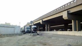 Trucks under bridge from a distance stock footage