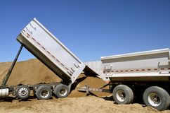 Trucks unload gravel at construction site. Royalty Free Stock Photography