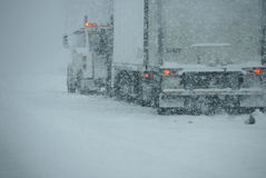 Trucks on winter highway during snowstorm Stock Photos
