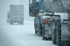Trucks on winter highway during snowstorm Stock Images