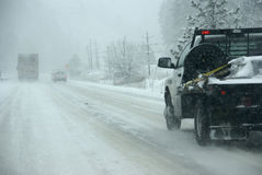 Trucks on winter highway during snowstorm Royalty Free Stock Image