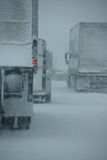 Trucks on winter highway during snowstorm Royalty Free Stock Photo