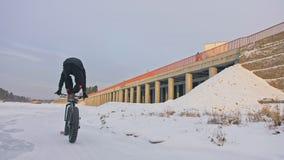 Truco acrobático Soporte en asiento de bicicleta mientras que la bici está en paseo Bici gorda del deportista del soporte extremo almacen de metraje de vídeo