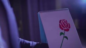 Truco con una rosa pintada que cambia color La rosa pintada da vuelta rojo Truco y sesión fotográfica de la demostración del mago almacen de video
