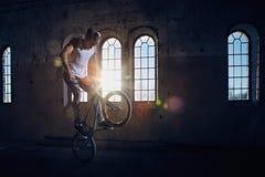 Truco de BMX y montar a caballo del salto en un pasillo con luz del sol Fotos de archivo libres de regalías