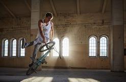 Truco de BMX y montar a caballo del salto en un pasillo con luz del sol Fotografía de archivo