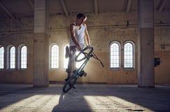 Truco de BMX y montar a caballo del salto en un pasillo con luz del sol foto de archivo libre de regalías