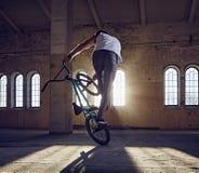 Truco de BMX y montar a caballo del salto en un pasillo con luz del sol Imagenes de archivo