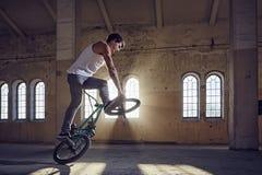 Truco de BMX y montar a caballo del salto en un pasillo con luz del sol Fotos de archivo