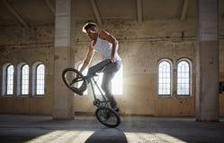 Truco de BMX y montar a caballo del salto en un pasillo con luz del sol imágenes de archivo libres de regalías