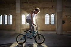 Truco de BMX y montar a caballo del salto en un pasillo con luz del sol Fotografía de archivo libre de regalías