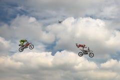 Truco del motocrós del estilo libre de dos motoristas en el fondo del cielo azul de la nube Quadrocopter quita el truco Alemán-St Fotos de archivo