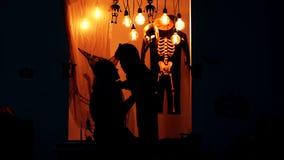 Truco o convite Concepto de la celebración de Halloween La familia en trajes se divierte el Halloween Silueta de una bruja y de u almacen de metraje de vídeo